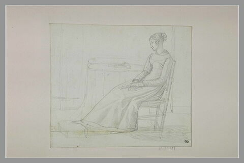 Jeune femme assise près d'une table
