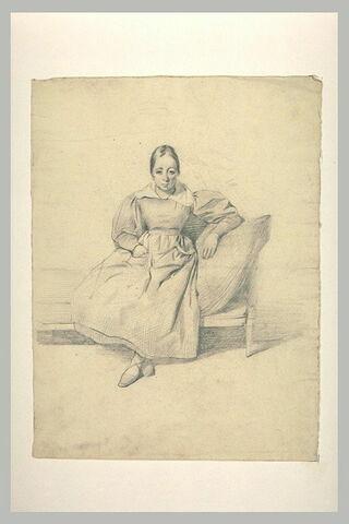Femme assise, sur un canapé, de face, les pieds croisés