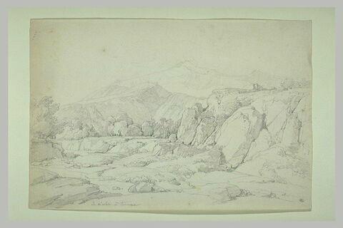 Torrent au-dessous de rochers sur un fond de montagnes
