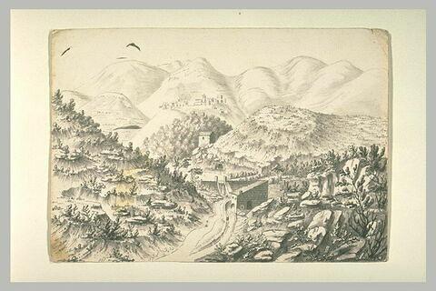 Vue d'un village dans les montagnes avec un moulin au premier plan.