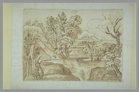 Etang dans un site boisé alimenté par une cascade, avec une ville au loin