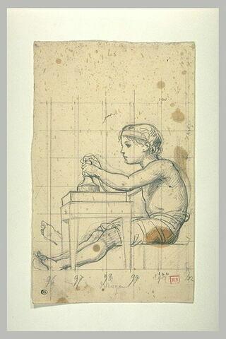 Jeune garçon, assis, de profil, devant une table