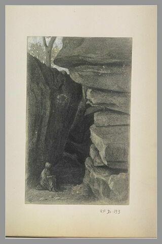 Femme assise auprès d'un bloc de roches