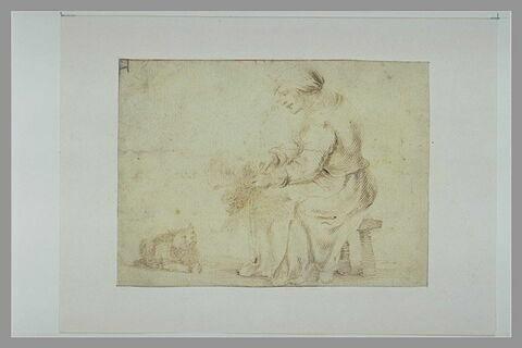 Femme assise, de profil, plumant une volaille devant un chat attentif