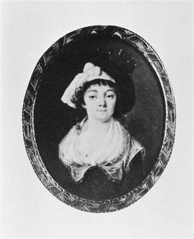 Portrait de femme vue à mi-corps de face,. Elle est coiffée d'un chapeau noir et vêtue d'une robe bleue à raies brunes