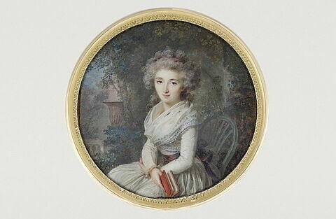 Portrait de femme assise dans un parc, tenant un livre