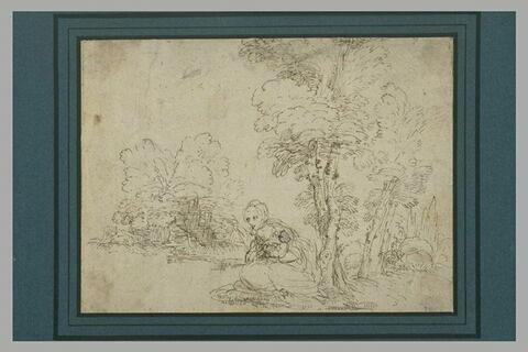 Femme accroupie tenant un bébé sous un arbre, dans un paysage
