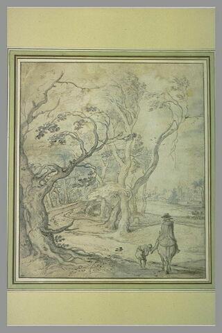 Garçon rajustant l'étrier d'un cavalier sur un chemin bordé de vieux arbres