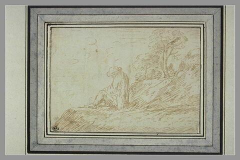 Homme assis, de dos, dans un paysage