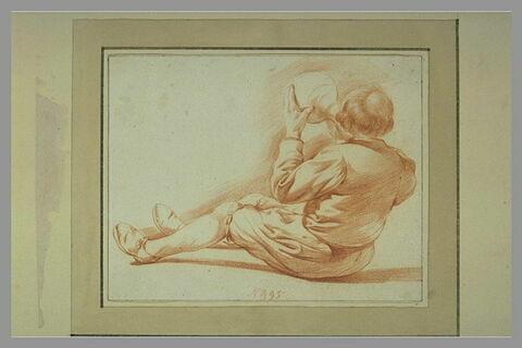 Homme assis à terre, buvant à un cruchon, vu de dos