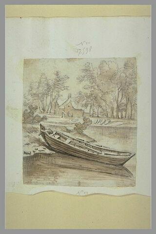 Barque sur la berge, amarrée devant des bâtiments entourés d'arbres