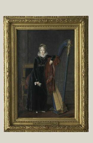 Portrait en pied d'une jeune femme blonde, en robe de velours noir accoudée à une harpe.
