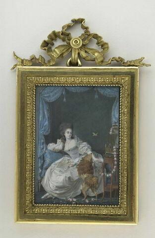 Jeune femme vêtue de blanc, assise sur un canapé bleu