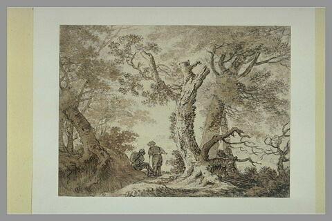 Deux hommes assis discutant, sur un chemin traversant une forêt