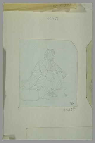 Oriental fumant, coiffé d'un turban et assis sur une pierre