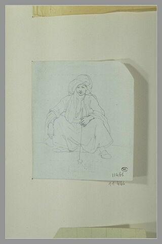Oriental fumant, coiffé d'un turban et assis sur le sol