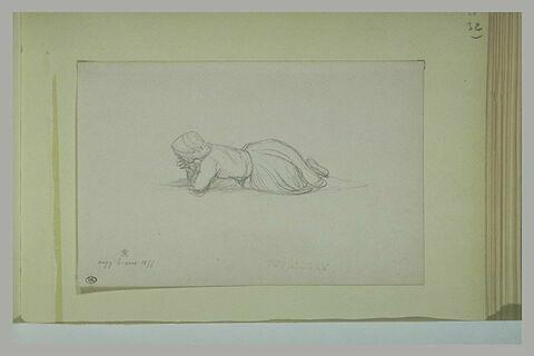 Femme couchée sur le ventre, le visage dans les mains