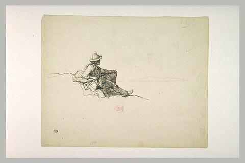 Un berger italien, assis par terre comtemplant des montagnes