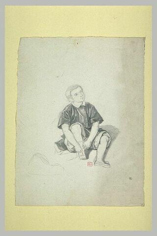 Jeune garçon, assis par terre, rattachant sa sandale droite