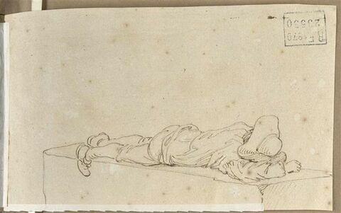 Homme couché sur le ventre, étendu sur une pierre