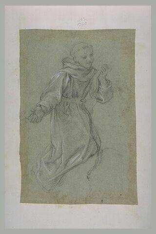 Un religieux à genoux comtemple une étoffe qu'il tient dans la main gauche