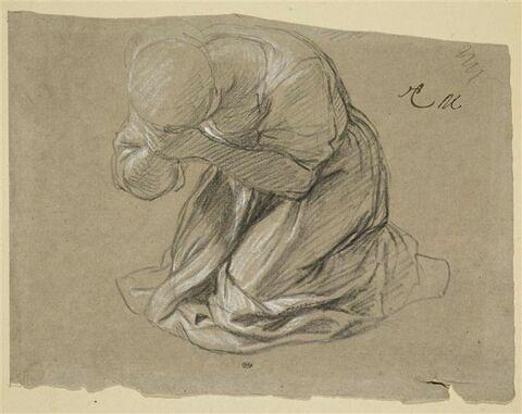 Femme à genoux, la tête cachée dans ses mains