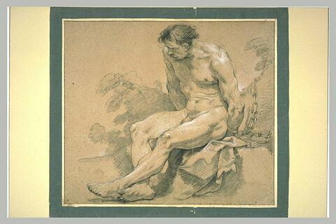 Homme nu, assis, enchaîné à un arbre