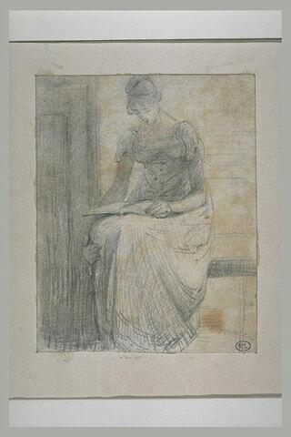Emma, assise de face, lisant sur ses genoux