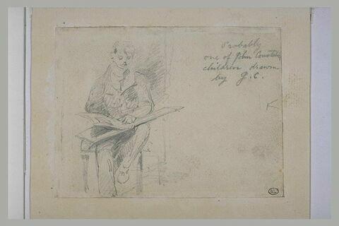 Jeune garçon assis sur une chaise, tenant un livre