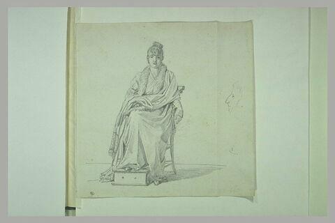 Jeune femme, assise, les pieds sur une chaufferette ; tête d'homme