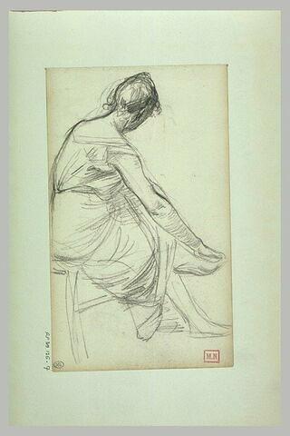 Femme assise sur une chaise, de dos, de trois quarts, les jambes croisées