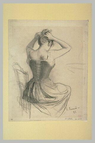Femme assise, vue de dos, se coiffant