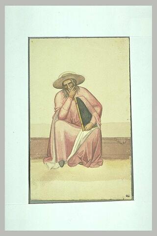 Homme coiffé d'un chapeau, assis, tenant un grand livre sous le bras gauche