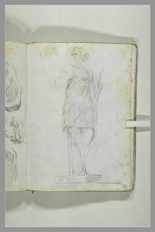 Jeune femme debout tenant une pomme dans la main droite, le bras replié, ...
