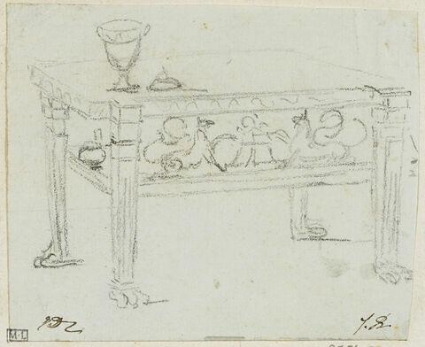 Un verre à pied posé sur une table basse, une frise en décore les bords