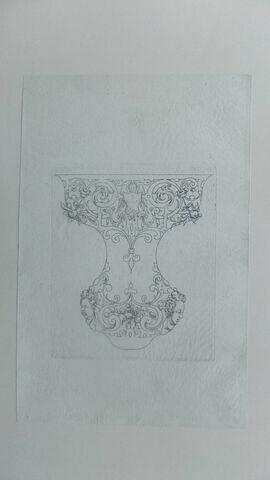 Ornement en forme de haut de vase avec deux têtes au bas