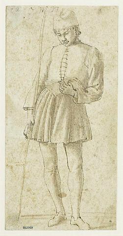 Jeune homme debout, tenant un bâton et lisant