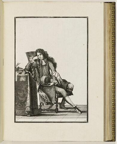 Un homme assis, le coude appuyé sur une table
